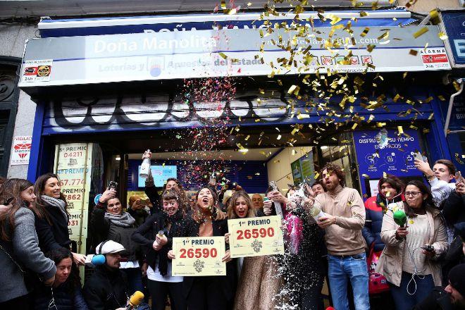 Un grupo de personas celebran en la administración madrileña de Doña Manolita el premio Gordo de la Lotería de Navidad. Durante el sorteo podrá comprobar aquí los premios de la  Lotería de Navidad.