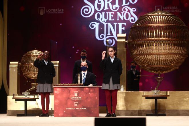 Dos de las niñas de la residencia de San Ildefonso, cantan uno de los quintos premios de la Lotería de Navidad.