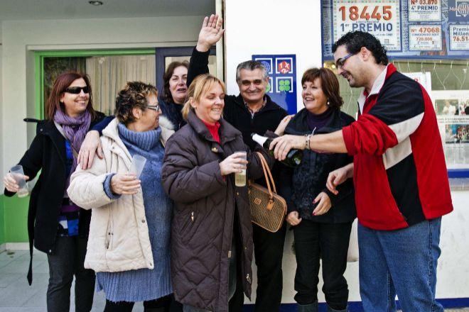 Un grupo de personas celebran un premio de la Lotería de Navidad. Durante el sorteo podrá comprobar aquí los premios de la Lotería de Navidad.