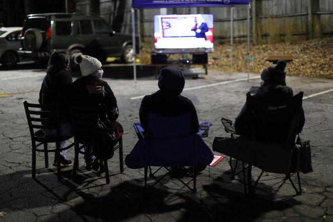 Un grupo de ciudadanos sigue el recuento en un aparcamiento en Atlanta (Georgia).