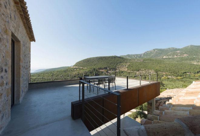 La escalera que da acceso a la primera planta de la vivienda continúa hasta la terraza con vistas a la montaña que desciende hasta la costa.