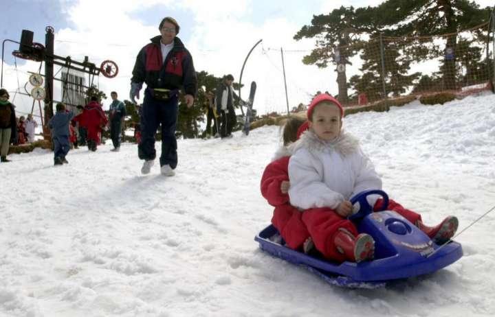 Unas niñas disfrutan sobre un trineo con volante en el puerto madrileño de Navacerrada.