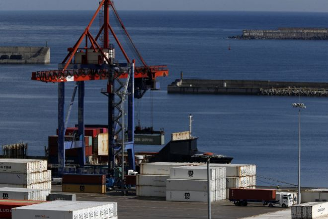 Una grúa carga contenedores en un barco mercante en el Puerto de Bilbao.