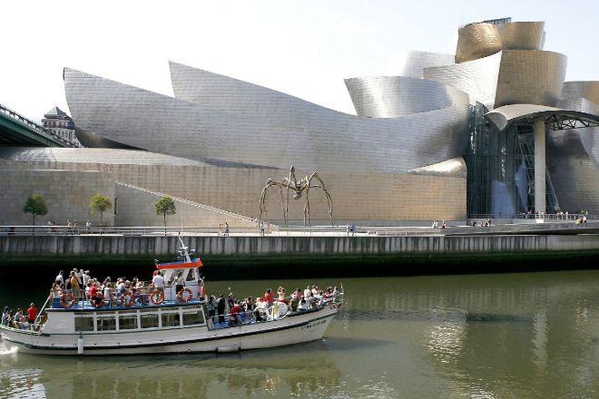 Un barco turístico realiza un paseo por la ría del Nervión, a su paso por el Museo Guggenhein de Bilbao.