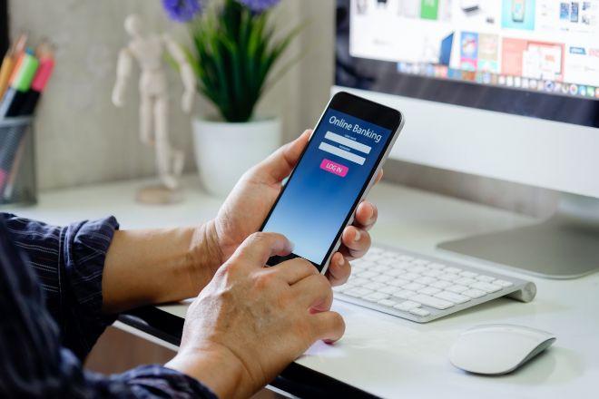 Un usuario de banca digital operando con su móvil desde casa.