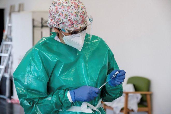 Una trabajadora prepara la segunda dosis de la vacuna