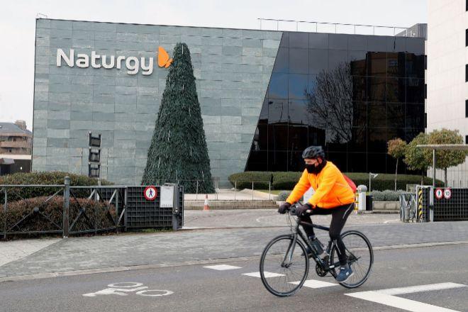 Un ciclista pasa ante la sede de la compañía energética Naturgy, en Madrid.