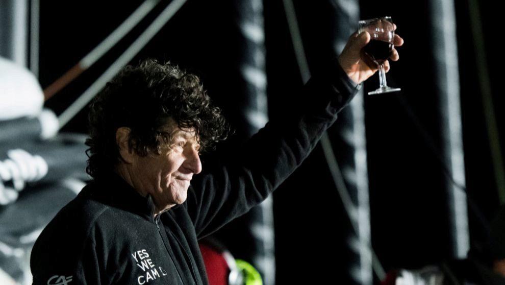 Jean Le Cam alza una copa de vino a bordo de su barco en su llegada a...