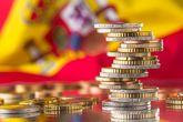 Monedas de euro con la bandera de España de fondo