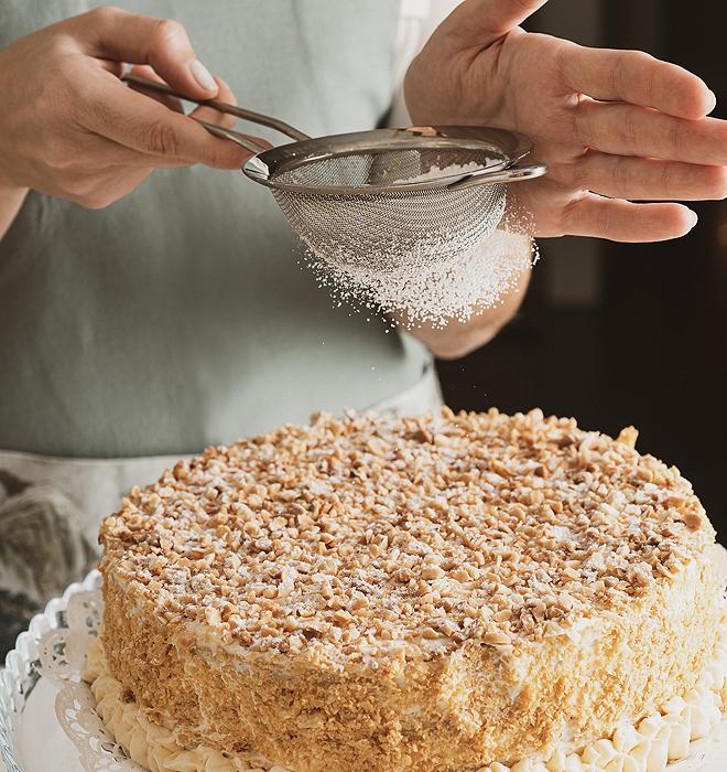 Últimos toques a una de las tartas de hojaldre almendradas características de Confitería Blanco.