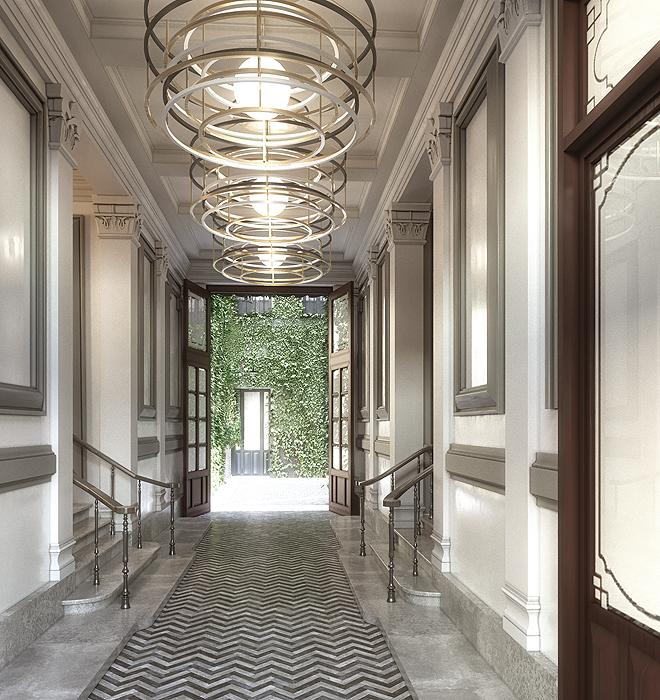 Entrada del edificio con escalera y patio que destaca como elementos clave el arquitecto del proyecto.