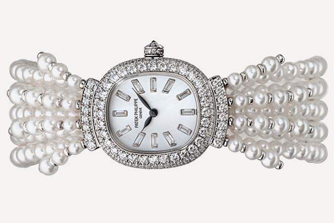 La esfera del reloj tiene incrustados diamantes talla baguette que hacen de índices horarios. La caja, hecha en oro blanco y recubierta de diamantes, es abrazada por hebras confeccionadas con perlas.