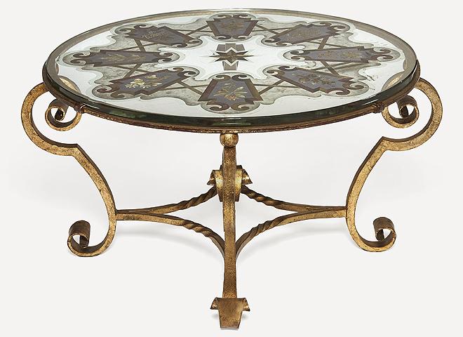"""Mesa baja de hierro forjado y dorado y vidrio """"églomisé"""". Mide 48,5 cm de alto y 82 cm de diámetro y tiene una estimación de entre 800 y 1.200 euros."""