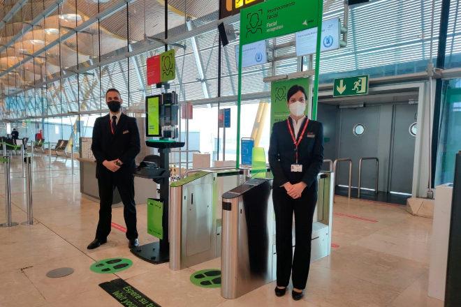Dos operarios de Iberia esperan para realizar el embarque biométrico de los pasajeros.