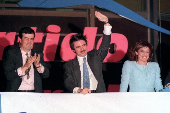 José María Aznar, flanqueado por Francisco Álvarez Cascos y Ana Botella, celebra desde el balcón de la sede del PP, en la madrileña calle Génova, la victoria del PP el 3 de marzo de 1996.