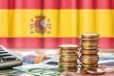 Monedas y billetes de euros con la bandera de España de fondo