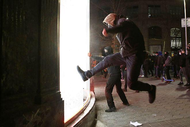 Manifestantes tratan de romper un escaparate de una tienda en el centro de Barcelona, durante las protestas por el encarcelamiento del rapero Pablo Hasél.