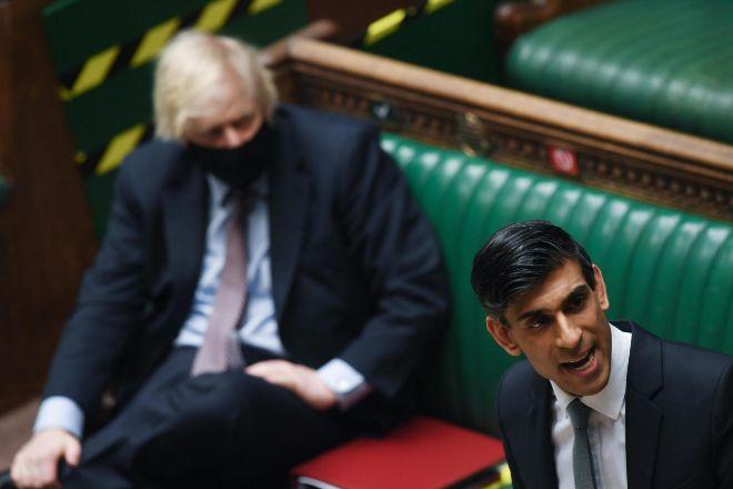 Rishi Sunak, el ministro de Economía de Reino Unido, y, al fondo, Boris Johnson, primer ministro.