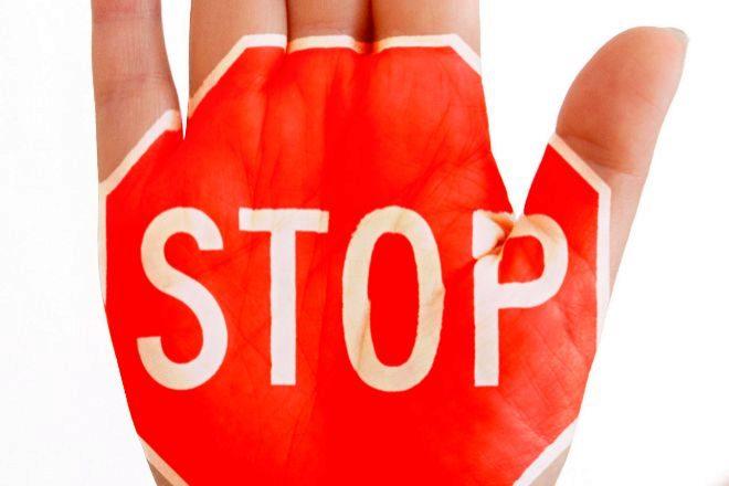 Señal de 'stop' dibujada en una mano