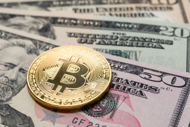 Moneda de bitcoin encima de billetes de dólar