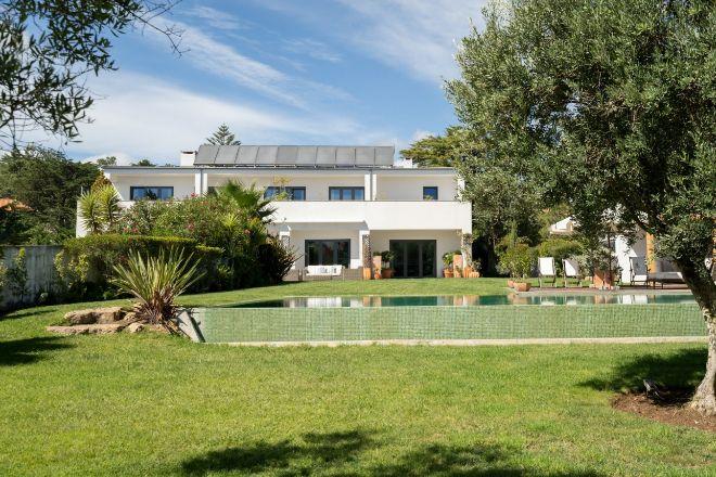 Ejemplo de vivienda en venta de MoRe Portugal, en zona premium de Estoril, con cinco dormitorios y un apartamento con entrada independiente, vistas al mar desde el jardín y el primer piso, tres pisos con ascensor, gimnasio y garaje para cinco coches. Precio: 3,98 millones de euros.