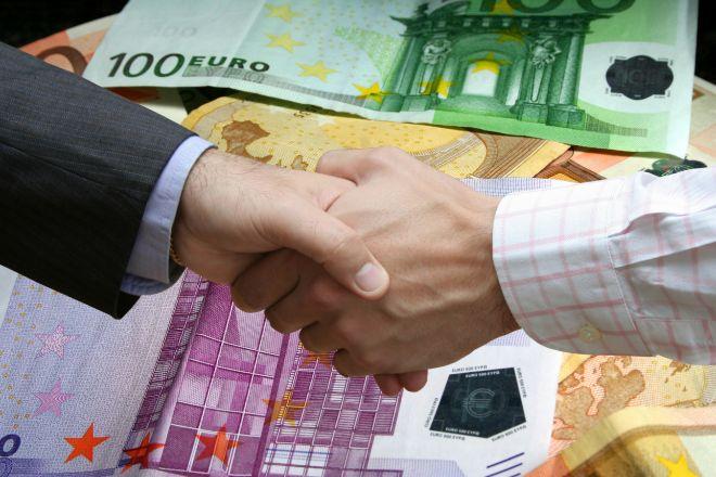 Apretón de manos entre ejecutivo y un empleado que simboliza una negociación salarial.