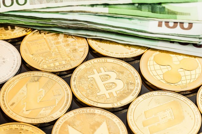 La criptomoneda Bitcoin y billetes de 100 euros