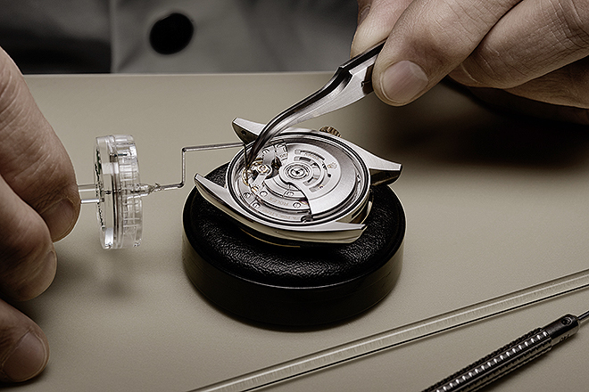 El relojero ajustando el volante del mecanismo.