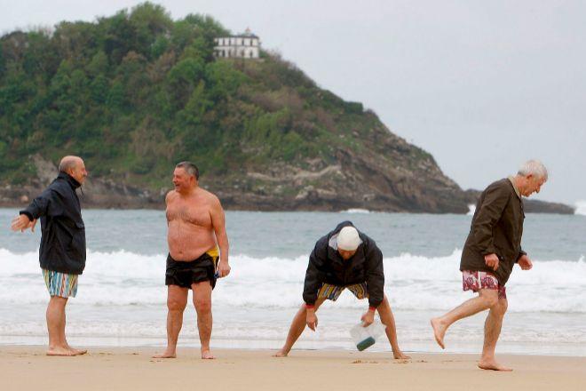 Unos jubilados hacen deporte en la playa de la Concha de San Sebastián en una imagen de archivo.