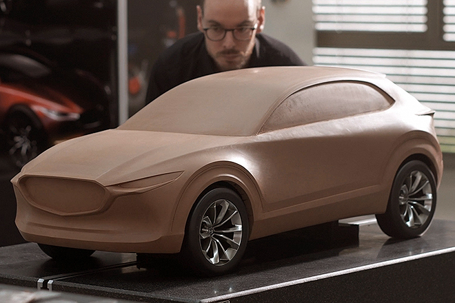 Uno de los escultores de arcilla del centro de diseño de Mazda en Oberursel observa el modelado de un Mazda CX30.