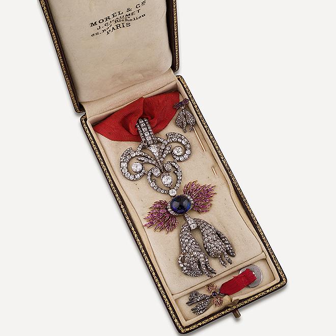 Caja original con el lote que sale a la venta, compuesto por por venera, insignia y alfiler.