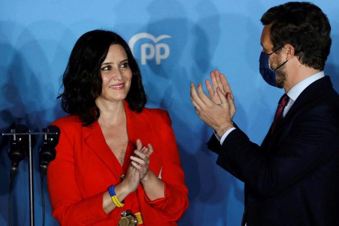 La presidenta de la Comunidad de Madrid y candidata por el Partido Popular a la reelección, Isabel Díaz Ayuso, acompañada por el presidente del partido Pablo Casado, en el balcón de la sede del partido en la calle Génova.