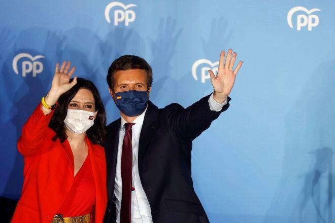 La presidenta de la Comunidad de Madrid y candidata por el Partido Popular a la reelección, Isabel Díaz Ayuso, acompañada por el presidente del partido, Pablo Casado, en el balcón de la sede del partido en la calle Génova.
