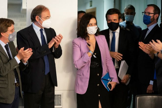 Isabel Díaz Ayuso, escoltada por Pablo Casado, recibe los aplausos de otros dirigentes del PP ayer en Génova.