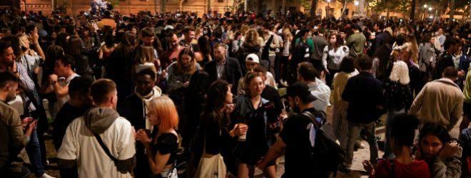 Decenas de jóvenes celebran junto al Passeig de Lluis Companys el fin del estado de alarma.