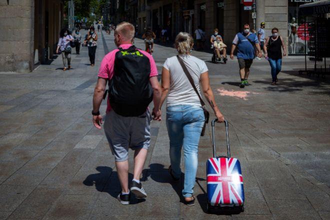 Una pareja de turistas  británicos caminan por el centro de Barcelona.