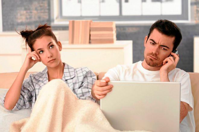 Un hombre trabaja desde la cama con su pareja al lado