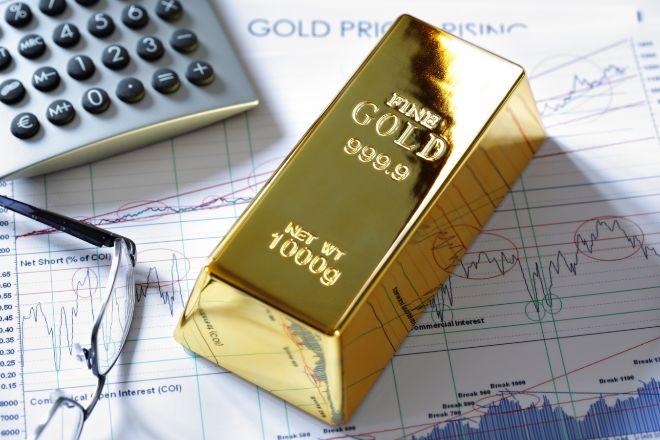 Imagen de un lingote de oro sobre gráficos bursátiles