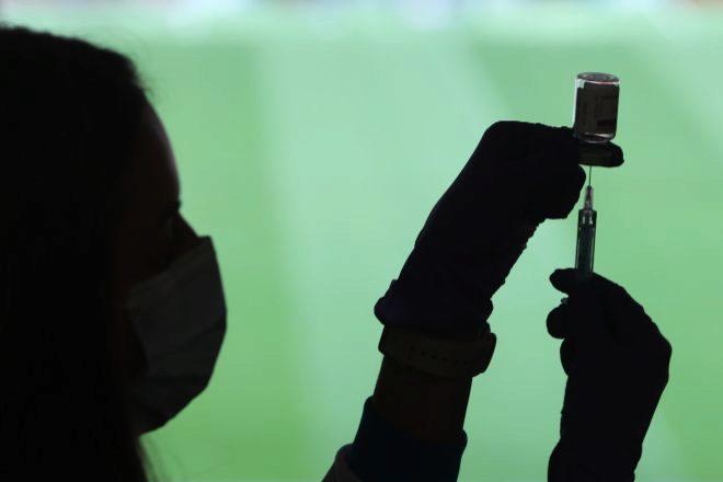 Un profesional sanitaria sostiene una jeringuilla y un vial con una vacuna contra el Covid en el Estadio Wanda Metropolitano, en Madrid (España) el pasado 30 de marzo de 2021.
