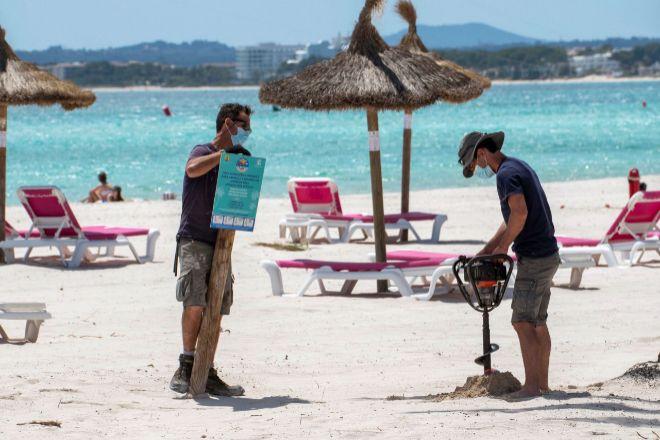 Puesta a punto de una playa de Mallorca para recibir turistas, ayer.