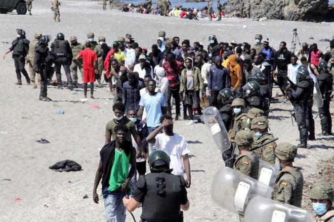 Soldados vigilan a un grupo de inmigrantes en la playa fronteriza de El Tarajal, en Ceuta.