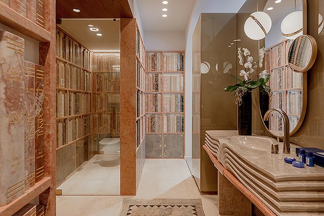 Baño del hotel con paredes de mármol que representan libros.