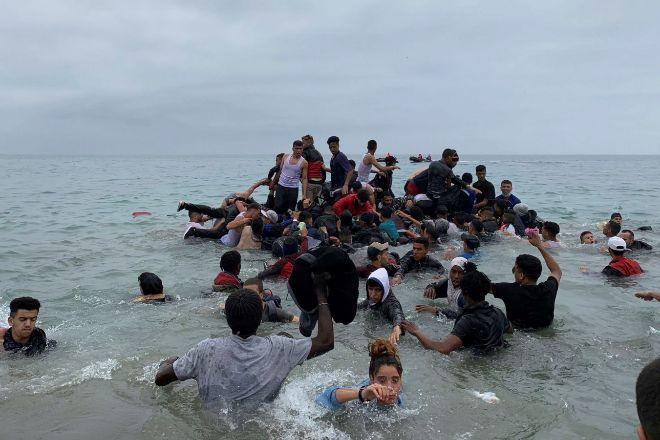 Un grupo de personas se hacen con una embarcación de las autoridades marroquíes en la playa de la localidad de Fnideq (Castillejos) para cruzar los espigones de Ceuta, la semana pasada, en una avalancha de inmigrantes sin precedentes en España.