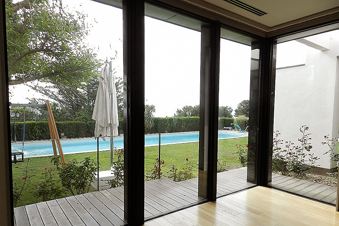 Vista del jardín y la piscina desde la parte interior de la casa