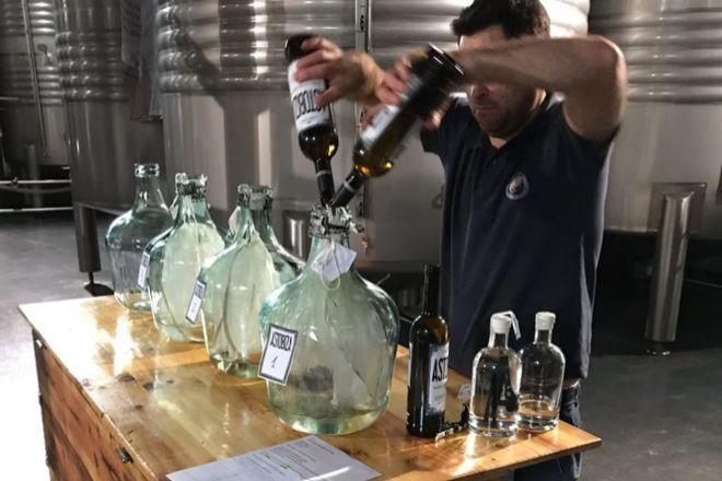 Un empleado de la Bodega Astobiza realiza pruebas de vermut en una damajuana.