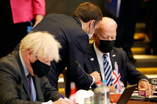 El presidente francés, Emmanuel Macron, se dirige al presidente de EEUU, Joe Biden, ante la atenta mirada del primer ministro británico, Boris Johnson, ayer en Bruselas.