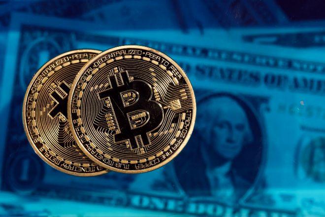 Monedas de bitcoin con billetes de dólar de fondo