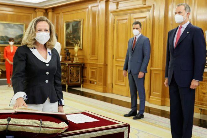 La vicepresidenta primera y ministra de Asuntos Económicos y Transformación Digital, Nadia Calviño, promete su cargo ante el Rey Felipe VI y el presidente del Gobierno, Pedro Sánchez, ayer en el Palacio de La Zarzuela.