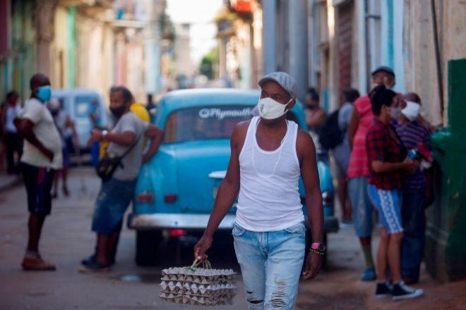 Un hombre camina por una calle de La Habana con cubetas de huevos.