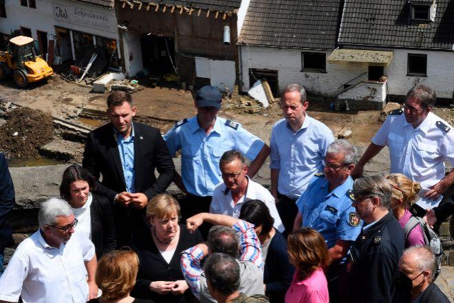 La canciller alemana, Angela Merkel (c), escucha a los afectados por las inundaciones.